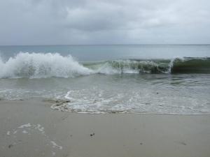 Waves in rolls sandy beach